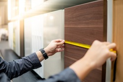 Male hand using tape measure on cabinet panel choosing materials or countertops for built-in furniture design. Shopping furniture and house decoration. Home improvement concept