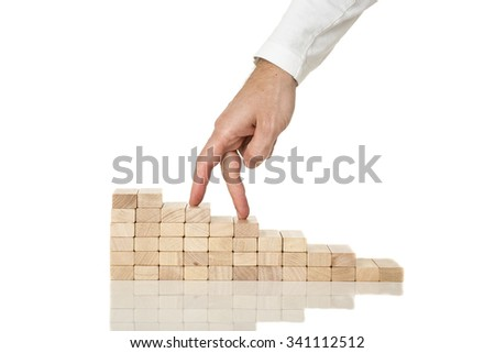 Male hand walking his fingers up wooden staircase made of pegs placed on white desk with reflection. #341112512