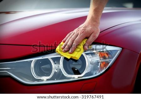 Male hand wiping car headlights