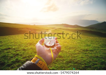 Male hand with a magnetic compass ea against the backdrop of a beautiful landscape at sunset. The concept of navigating the search for your own path and orientation to the cardinal points Stockfoto ©
