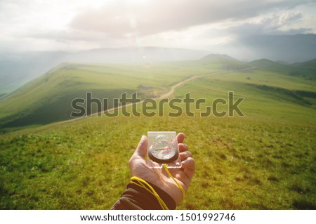 Male hand with a magnetic compass ea against the backdrop of a beautiful landscape at sunset. The concept of navigating the search for your own path and orientation to the cardinal points #1501992746