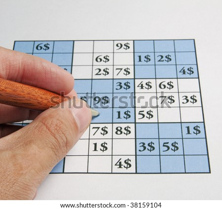 Male hand with a pen over a sudoku with dollar symbols