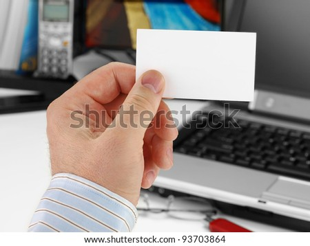 Male hand with blank business card in color white in front of office background