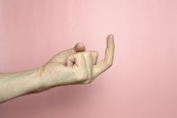 Male hand with fair skin shows a gesture, hand on a light pink background. Gesture finger, bent forefinger. Stock photo for web and print.