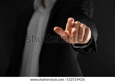 Male hand with finger pointing on dark background #532519426