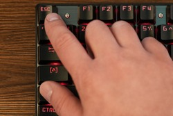 male hand with index finger presses escape key on black keyboard with red backlight