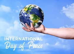 Male hand with model of Earth outdoors. International Day of Peace