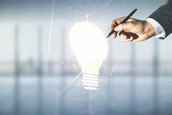 Male hand with pen draws abstract virtual light bulb illustration on blurred office background, future technology concept. Multiexposure