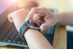 Male hand with smart watch on wrist, wearable watch and technology computer laptop for communication, checking time.