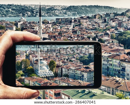 Male hand with smartphone taking a picture of Istanbul. Tourism concept.