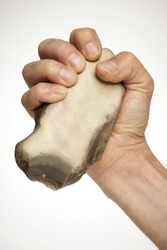 Male hand with stone fist wedge used as a tool or weapon