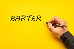 Male hand writes in black pen the word barter on a yellow background with copy space. Business concept photo
