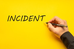 Male hand writes in black pen the word incident on a yellow background with copy space. Business concept photo