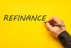 Male hand writes in black pen the word refinance on a yellow background with copy space. Business concept photo