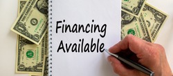 Male hand writing 'financing available' on white note, on white background. Dollar bills. Business concept.