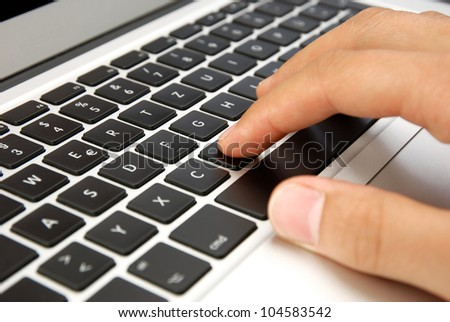 male hand writing on laptop design keyboard with black keys