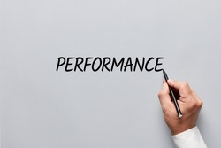 Male hand writing the word performance on gray background. Assessing job, work or business performance concept.