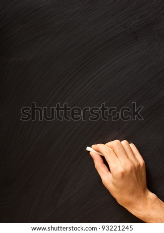 Male hand writing with chalk on a clean blackboard - add your own chalk!