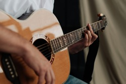 male hands and guitar close-up musician playing acoustic guitar. Music