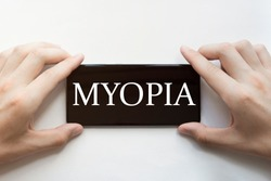 male hands are holding black phone with text MYOPIA on white background