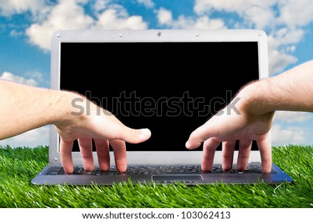 male hands are working on laptop on grass outdoors
