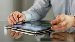 Male hands booking tickets, paying bill online on tablet PC