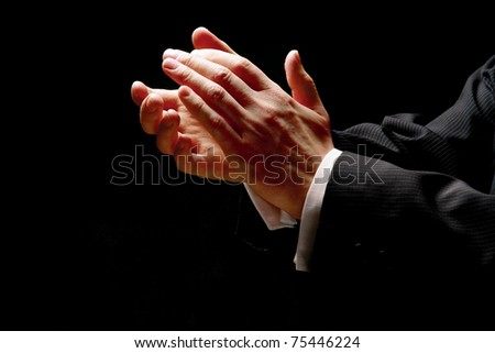 Male hands clapping on black