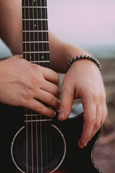 Male hands close up on black acoustic guitar. Outdoor