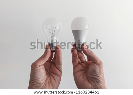 Male hands compare an incandescent light bulb and a LED lamp