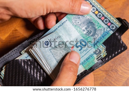 Male hands counting 50 Ringgit Malaysia in a leather wallet on a wooden table. RM50 in mans hand. Malaysian Ringgit shown by young man in a wallet. Close up to Malaysian currency.