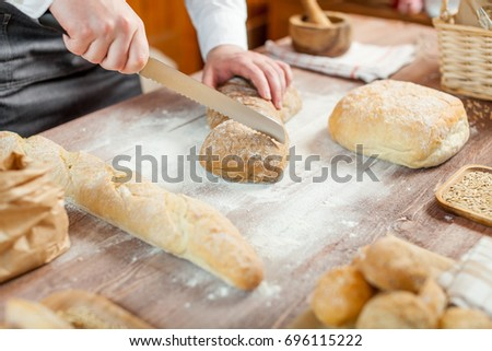 Male hands cutting fresh bread on the wooden table, selective focus - Shutterstock ID 696115222
