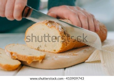 Male hands cutting wheaten bread on the wooden board, selective focus
