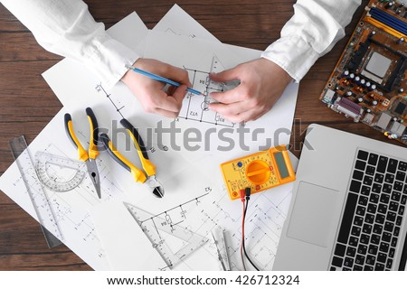 Male hands drawing electrical blueprint at wooden table, top view