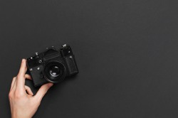 Male hands hold old vintage camera on black background top view flat lay with copy space. Concept for the photographer, old photographic equipment, minimalistic style