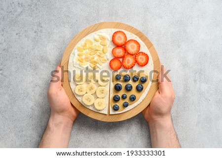 Male hands hold Tortilla with different fillings of peanut butter, banana, strawberry, blueberry, almond. Food trend. Sweet sandwich for breakfast. Trendy way of wrapping. Top view Foto stock ©
