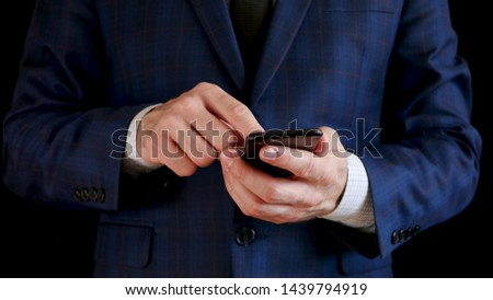 Male hands holding a black smartphone close up. Fingers touch the touchscreen of the phone #1439794919
