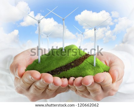 Male hands holding a green hill with wind turbines