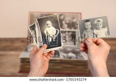 male hands holding an old retro album with vintage monochrome photographs in sepia color 1964-1965, the concept of genialogy, memory of ancestors, family ties, childhood memories Stockfoto ©