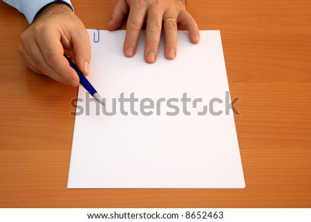 Male hands holding ballpoint pen pointing at blank document to sign