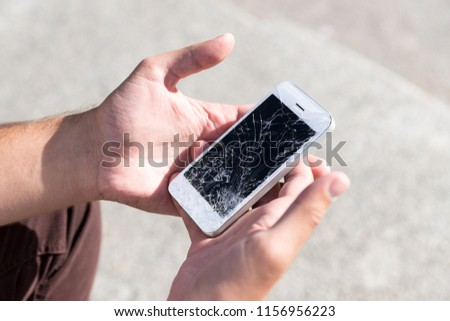 Male hands holding broken mobile smartphone after drop, view from above, outdoors. Smart phone with broken (cracked) screen. Picking broken phone from the floor.