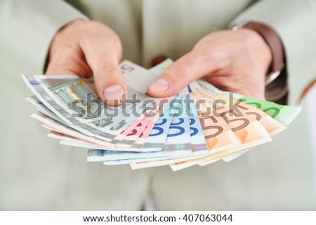 Male hands holding euros closeup #407063044