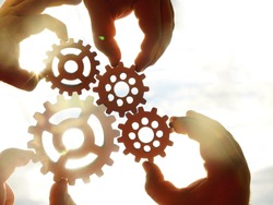 Male hands holding  four 4 wooden cog wheels, gear wheels on  sunny sky background. family concept.