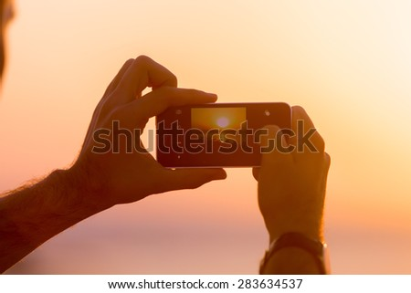 Male hands holding mobile phone with image of sunset or sunrise on the screen, taking photo in picturesque sea scenery, back view, close up