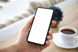 male hands holding phone with isolated screen over a table in the room