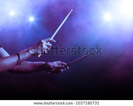Male hands holding two drum sticks. Smoky backgroung. Backlit