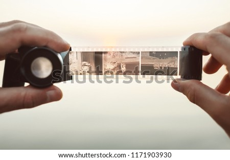 Male hands image using the Old vintage 35mm film Negative Viewer to see a frames on the sunset background #1171903930