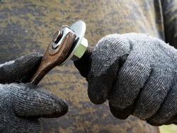 Male hands in gloves tighten the nut on the bolt with a wrench