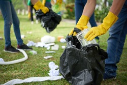 Male hands in yellow rubber gloves putting household waste into small bin bag