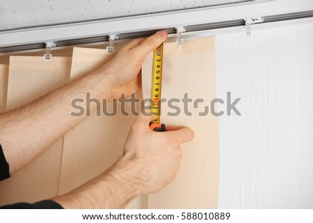 Male hands measuring vertical blinds