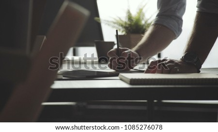 Male hands of an architect against the background of a large window. Man makes notes, writes with a pencil, leaning on the table: close-up. Man works in loft office with papers, drawings and documents Stock photo ©